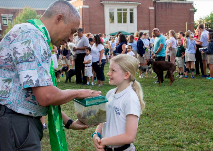 Head chaplain blessing a pet for a student.